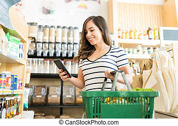 Customer Using Phone While Shopping In Supermarket