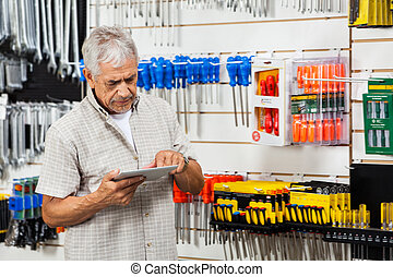 Customer Using Tablet Computer In Hardware Shop