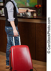Customer With Baggage Ringing Bell At Reception Counter
