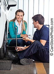 Customer With Mechanic Fixing Tire At Garage