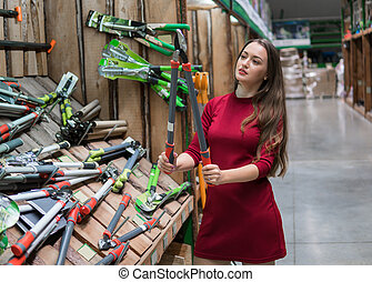 Customer woman buy garden maintenance tools.