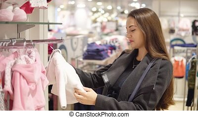 Customer woman choosing baby clothes in the shop - Customer...