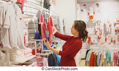 woman choosing baby clothes or children's wear in the shop -...