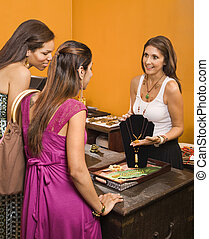 Customers and sales clerk. - Sales clerk showing necklace to...