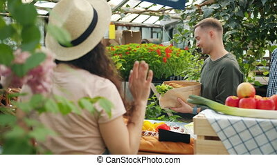 Customers buying organic food in greenhouse sale talking to...