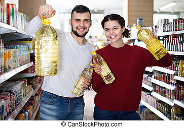 Smiling positive customers choosing seed-oil in plactic packing at shop