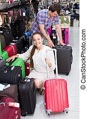 Customers choosing suitcases in store