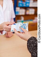 Customer's Hand Paying Money To Pharmacist