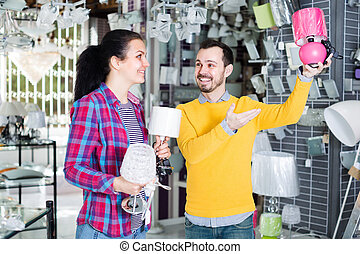 Customers in shop of home appliances are choosing night lamp