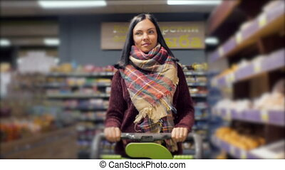 Customers shopping in supermarket, focus on woman with shopping cart. Slow motion
