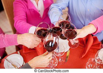 Customers Toasting Wine Glasses At Restaurant Table -...
