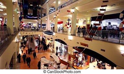 Customers walk along boutiques on multiple floors trade center Atrium at Kurskaya