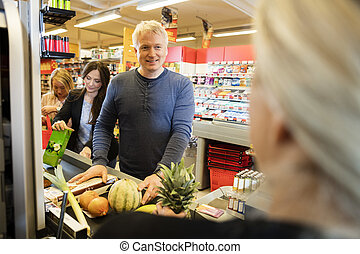 Customers With Products Standing At Checkout Counter