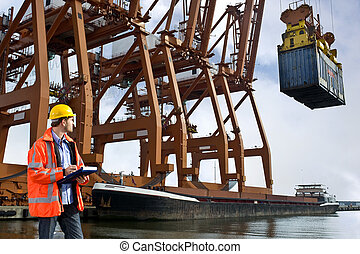 A customs officr checking containers being unloaded at a commercial harbor