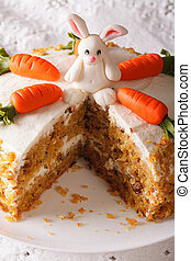Cut a piece of carrot cake decorated with bunny close-up. Vertical