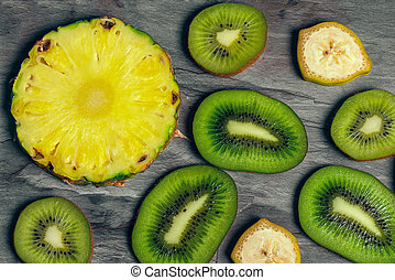 Cut and sliced fruits - pineapple, kiwi, banana. View from above
