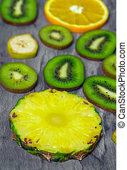 Cut and sliced fruits - pineapple, kiwi, orange, banana. View from above