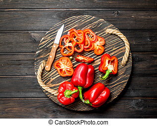 Cut and whole fresh sweet pepper on tray with knife.