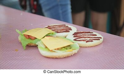 Cut buns for burgers with ketchup, cheese and lettuce