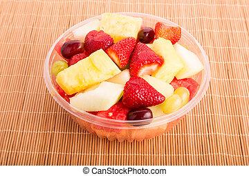 A plastic bowl of fresh cut fruit