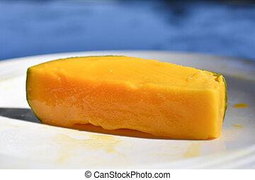 Cut juicy mango fruit in a plate on the beach