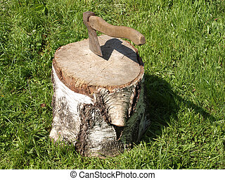 Cut log fire wood and old axe.