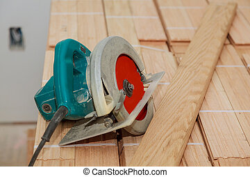 Cut old parquet floor with electric saw