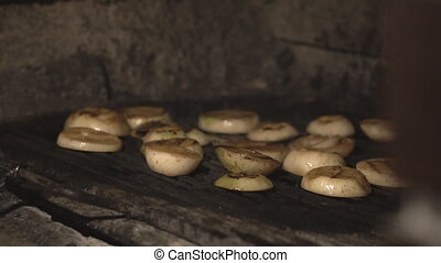 cut onions are fried on barbecue grill in masonry oven over...