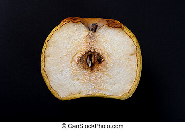 cut out section of an overripe pear on black background