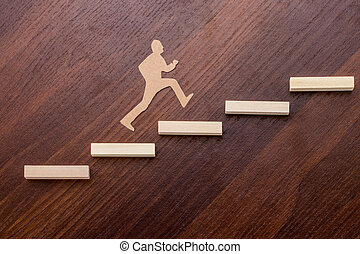 Cut outs of paper man climbing the steps to success in a conceptual image over wooden background