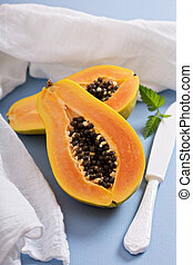Cut papaya on a blue table - Cut papaya exotic fruit on a...