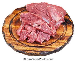 cut raw meat on cutting wooden board