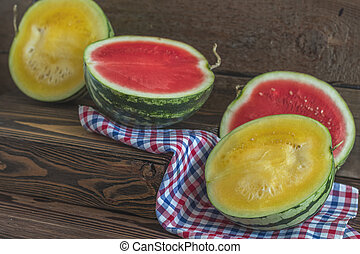Cut red and yellow watermelons on a wooden box in a vintage wooden background in rustic style, selective focus, toned photo.