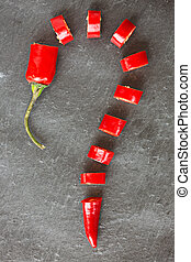 Cut red chilly pepper in shape of question mark, on gray...