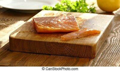 Cut salmon fillets on a cutting board and spread on a plate....
