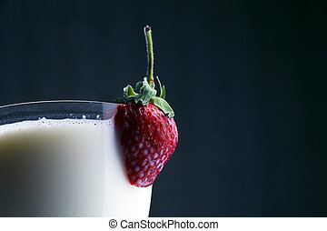 cut strawberries in a glass with milk