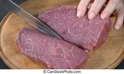Cut the meat on a cutting board. slow motion