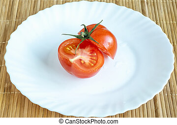 Cut tomato on white plate