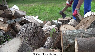 Cut tree trunk pile and blurred worker man chop wood with...