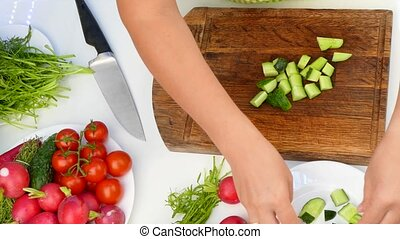 Cut vegetables on the chalkboard - hand cuts a cucumber on...