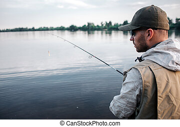 Cut view of fisherman stands with his back on camera. He is looking to the right. Guy has fly rod in hands. It is chilly outside so man wears sweater, vest and cap.