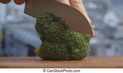 Cut with a knife on a wooden board closeup broccoli in the ...