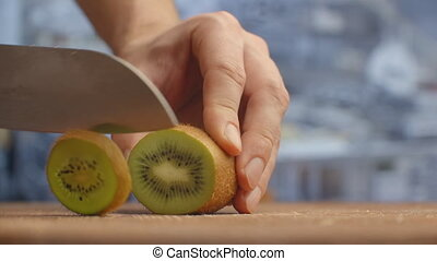 Cut with a knife on a wooden board closeup kiwi in the ...