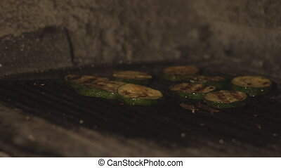 cut zucchini or courgette is cooked on the bbq grill in oven...