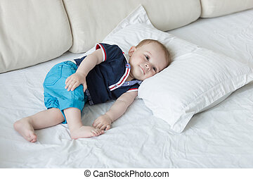 1 year old baby boy lying on big pillow on bed