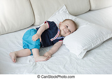 Cute 1 year old baby boy relaxing on big pillow