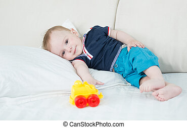 1 year old baby boy resting on bed after playing with toys