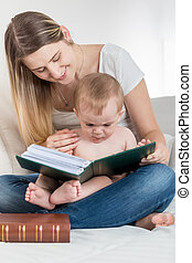 Cute 1 year old baby boy sitting on mothers lap and reading big old book