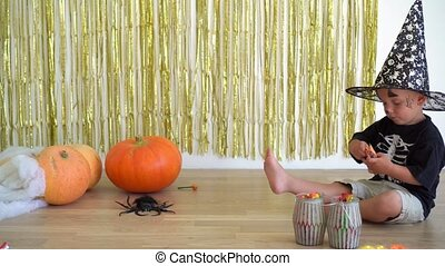 Cute 2 years old boy with magician wizard hat unpacking candy sweet sitting near pumpkins. Halloween celebration at home. Camera motion shot with gimbal.
