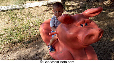 Cute 2 years old kid riding the pig in the park